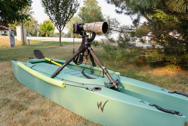camera with telescopic lens mounted on stable kayak for photography