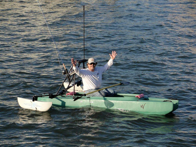 fly_fisherman-sitting_in_his_kayak_waving