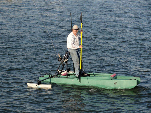 fly_fisherman_standing_on_top_of_his_kayak_with_outriggers_Florida