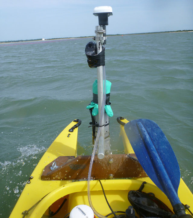motorized fishing kayak ploughing the waves with scientific gear mounted in front