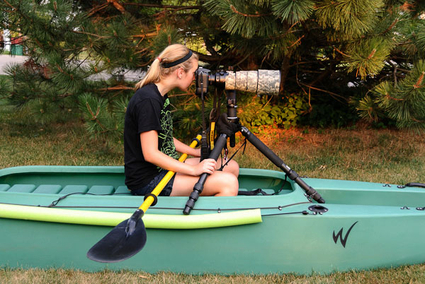 wildlife photographer looking through telescopic lens in stable kayak